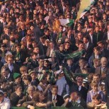 Celtic fans 1960s or 70s in colour scarves and tricolours